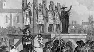 An illustration shows heretics being tortured and nailed to wooden posts during the first Inquisition.