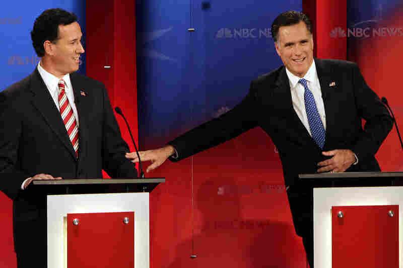 Mitt Romney motions toward Rick Santorum during an exchange.
