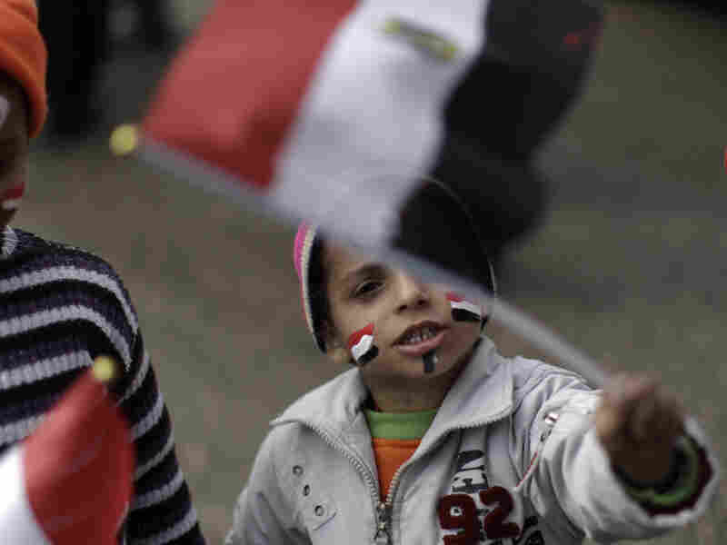 Mohammed Ahmed, 3, his face painted with the Egyptian national flag, waves a small flag during a protest Monday in Cairo's Tahrir Square.