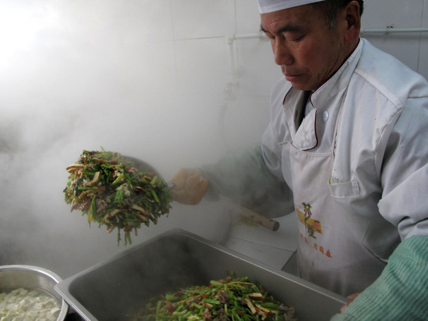 In the school kitchen, a cook uses a shovel for stir-frying. He is preparing meals for more than 200 students.
