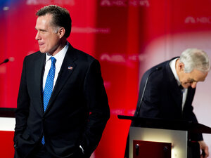 Mitt Romney stands on the stage during a commercial break as Republican presidential hopefuls take the stage for the  Debate at the University of South Florida, Jan. 23, 2012, Tampa, Florida. Romney has suffered under attacks about his time at Bain Capital.