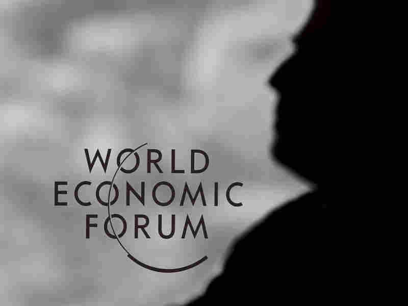 A guard stands next to a logo of the World Economic Forum at the Congress Center in the Swiss resort of Davos.