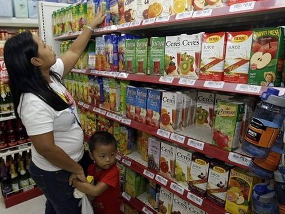 A woman with her son checks labels on fruit drinks in a store in Manila, Philippines.