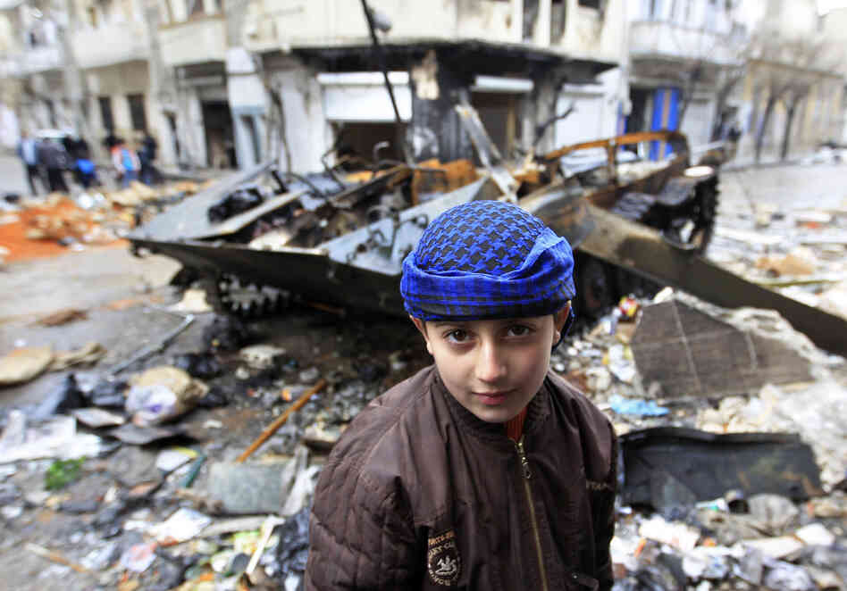 A Syrian boy stands in front of a damaged armored vehicle be
