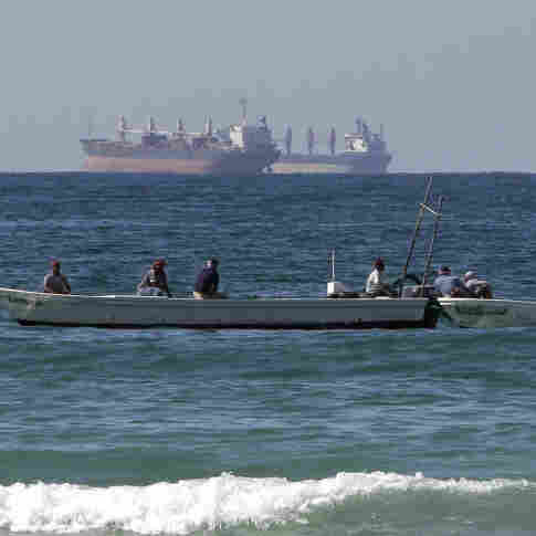 Fishing boats are seen in front of oil tankers on the Persian Gulf waters, south of the Strait of Hormuz. The European Union has announced plans to join U.S. efforts to slow the flow of oil from Iran, the world's third largest exporter.