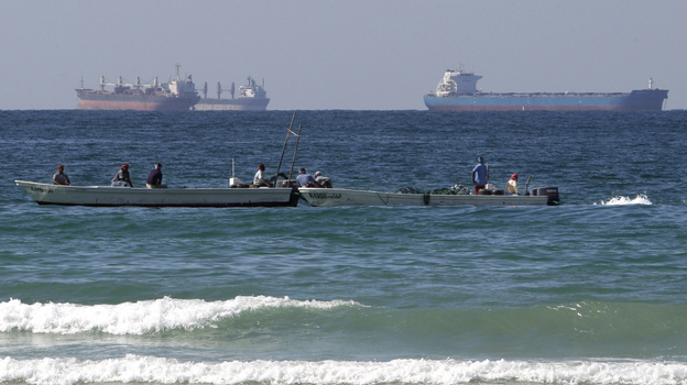 Fishing boats are seen in front of oil tankers on the Persian Gulf waters, south of the Strait of Hormuz. The European Union has announced plans to join U.S. efforts to slow the flow of oil from Iran, the world's third largest exporter.  (AP)