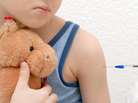 A boy holding a stuffed animal gets  immunized.