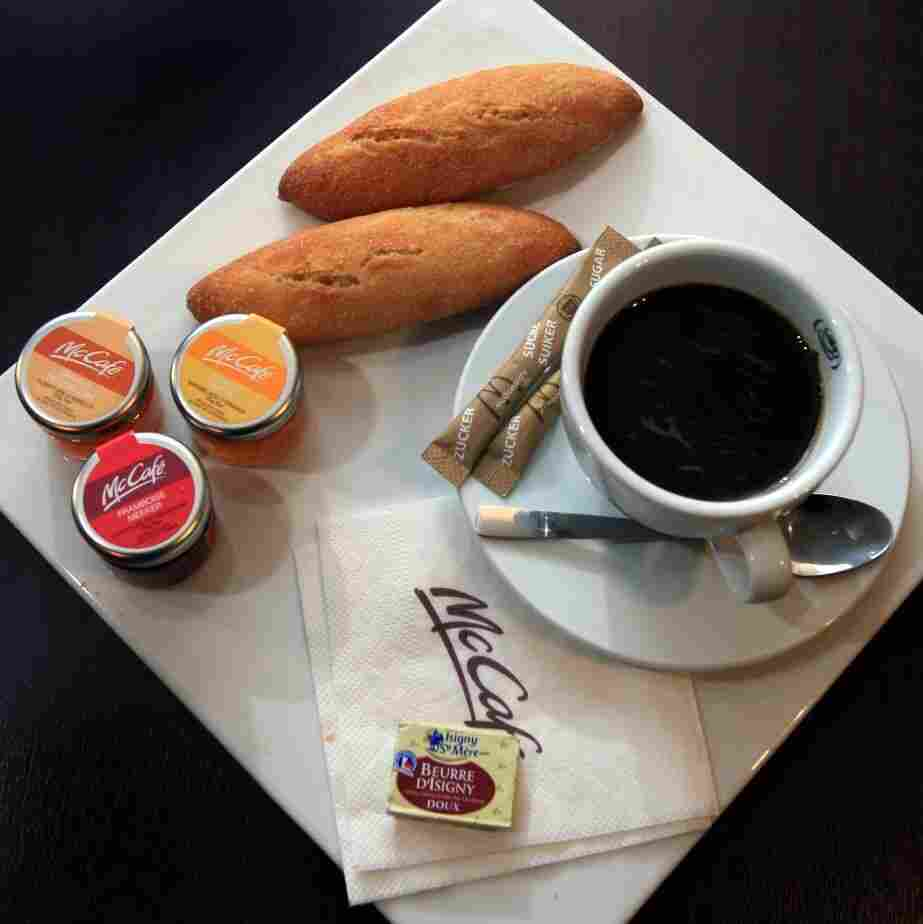 A McDonald's breakfast meal in Villeurbanne, France includes fresh baguettes and jam spreads with coffee for $4.55.