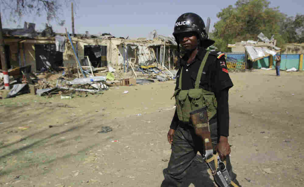 A police officer walks past the ruins of a market outside the state police headquarters in Kano, Nigeria, on Tuesday.