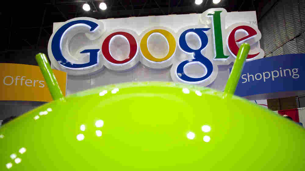 A sign for Google is displayed behind the Google android robot, at the National Retail Federation in New York.
