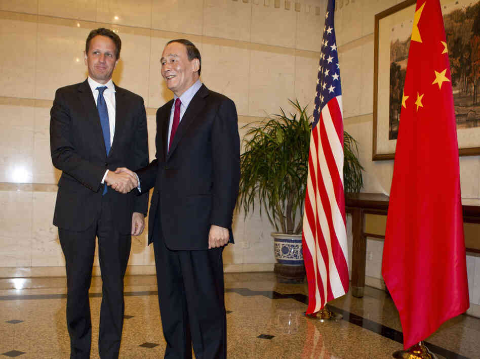 BEIJING, CHINA - US Treasury Secretary Timothy Geithner (L) shakes hands with Chinese Vice Premier, Wang Qishan before attending a dinner at the Diaoyutai State Guesthouse on January 10, 2012 in Beijing, China.