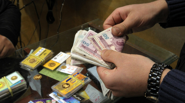 An Iranian man counts banknotes after exchanging a gold coin for cash in Tehran on Monday. Gold coins were being exchanged for over 10 million rials as the Iranian currency continues to lose value against the U.S. dollar. (AFP/Getty Images)