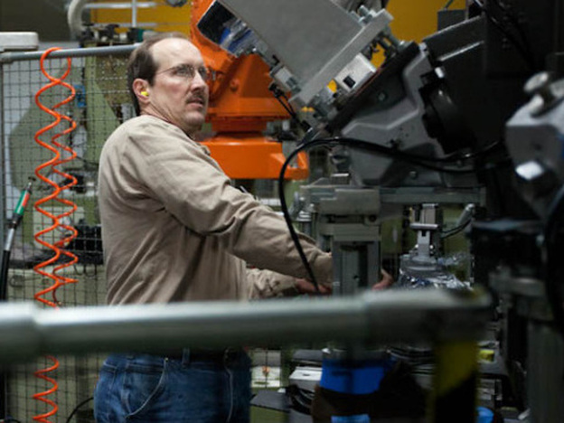 Tom Fitzgerald (left) and Shawn Dietel (center) look on as Richard Dietel operates a machine at Keen's shoe factory in Portland, Ore. The 15,000-square-foot facility houses two production lines.