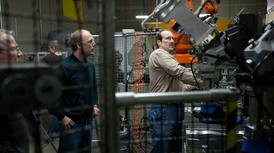 Tom Fitzgerald (left) and Shawn Dietel (center) look on as Richard Dietel operates a machine at Keen's shoe factory in Portland, Ore. The 15,000-square-foot facility houses two production lines. (Courtesy of Keen)