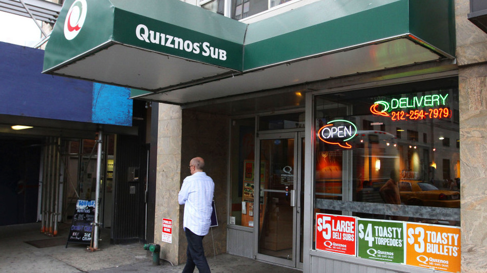 A man walks by a Quiznos franchise in New York City. The sandwich chain has given up part of its ownership to a private equity firm in order to restructure its debt and avoid bankruptcy.