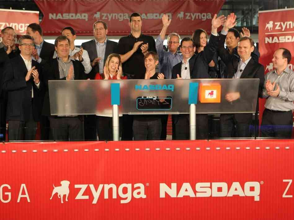 Zynga went public in December 2011. Mark Pincus (center) and his wife Ali Pincus (left), surrounded by Nasdaq and Zynga staff. The stock price fell on opening day. It was a bust, and has raised questions about the company's real value.