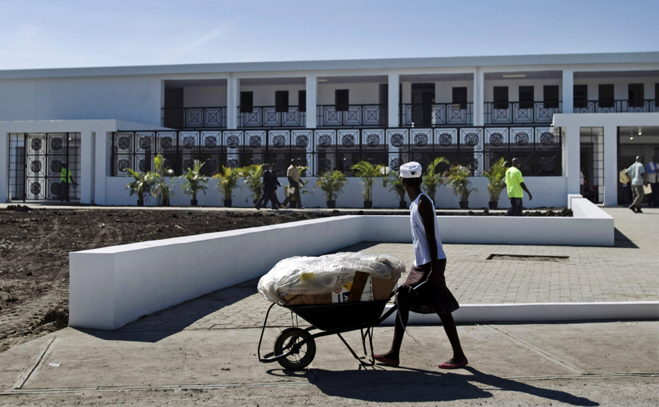 A worker pushes a wheelbarrow past the new National Teaching Hospital in Mirebalais, Haiti, on Jan. 10. When it opens this summer, the 320-bed facility will be Haiti's largest hospital and provide services and a level of care well beyond what's currently available. (Dieu Nalio Chery/AP)