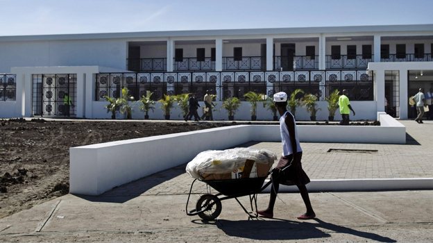 A worker pushes a wheelbarrow past the new National Teaching Hospital in Mirebalais, Haiti, on Jan. 10. When it opens this summer, the 320-bed facility will be Haiti's largest hospital and provide services and a level of care well beyond what's currently available. (AP)