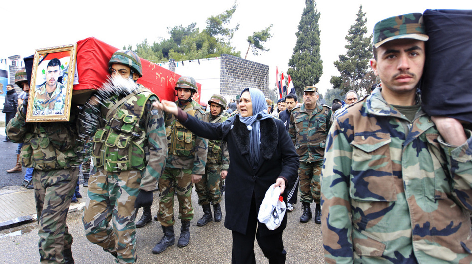 A woman throws rice as a Syrian soldier carries the coffin of a comrade during a funeral at the military hospital in Homs, Syria, this week. The soldiers were killed by gunmen, a Syrian government official said.