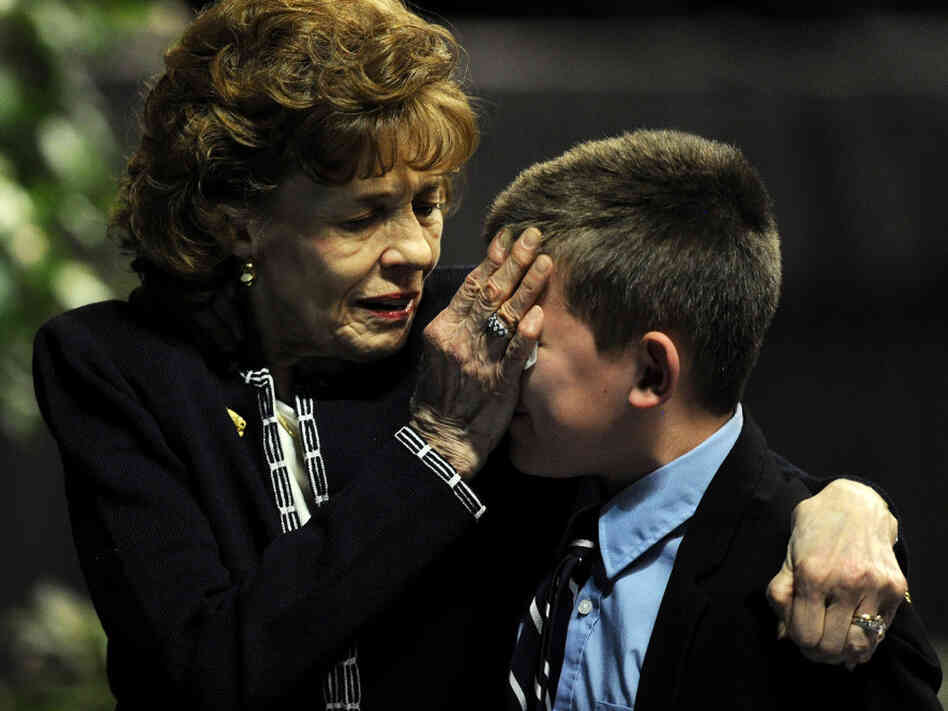 Sue Paterno, widow of Joe Paterno, consoles one of her grandsons following the memorial  service.