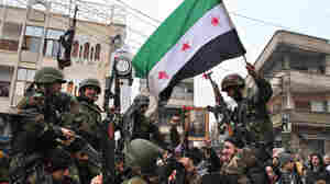 Syrian army defectors wave the Syrian revolution flag Thursday, shortly after they defected to join the anti-regime protesters.