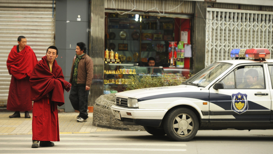 Ethnic Tibetan monks (left) walk past police vehicles on a street in Chengdu in China's Sichuan province Thursday. The Tibetan-inhabited region of West Sichuan appeared to be under lockdown after recent clashes.