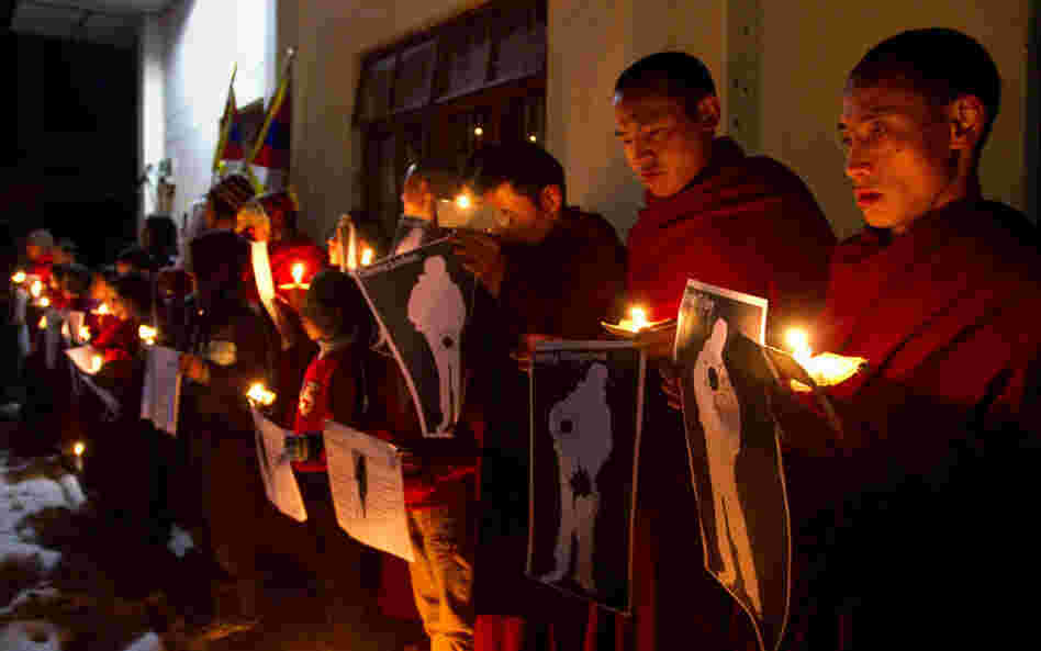 During a candlelight vigil in Dharamsala, India, on Wednesday, Tibetan Buddhist monks hold pictures of Tibetans they say were shot by Chinese security forces earlier this week.