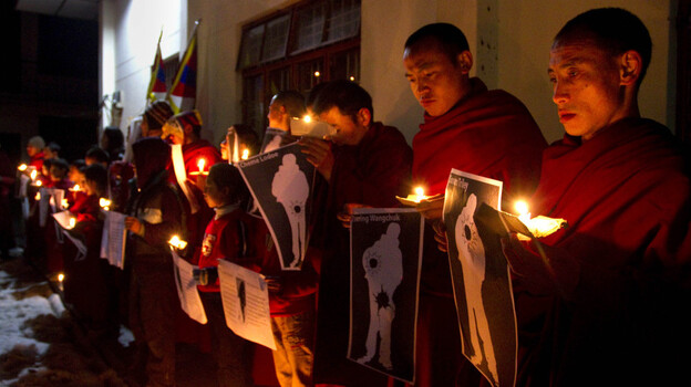 During a candlelight vigil in Dharamsala, India, on Wednesday, Tibetan Buddhist monks hold pictures of Tibetans they say were shot by Chinese security forces earlier this week.  (AP)