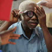 A man from Liberia uses a pump to adjust his liquid silicon lens. Liquid-lens glasses are part of an effort to make eyewear more accessible in the developing world.