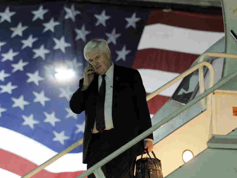 GOP presidential candidate Newt Gingrich speaks on a mobile phone as he arrives on a charter plane on Jan. 27 in Miami, Fla.