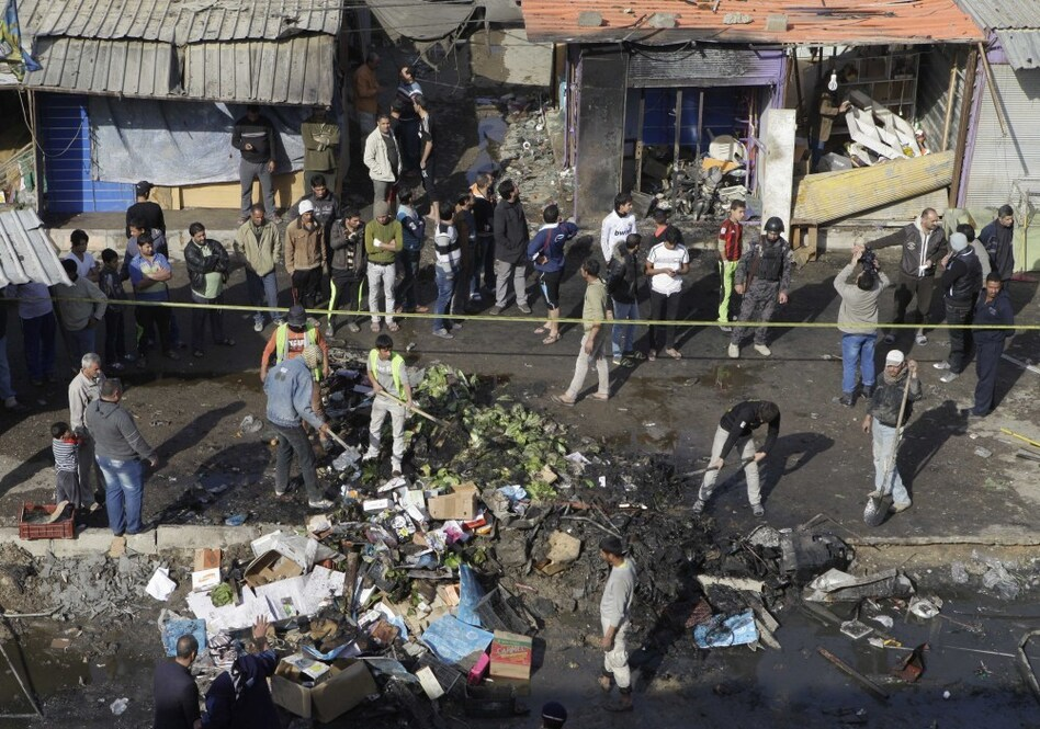 People gather at the scene of a car bomb attack in Zafaraniyah, <a></a>Baghdad, Iraq on Friday. A suicide bomber detonated an explosives-packed car near a funeral procession killing and injuring dozens of Iraqis, police said. (Khalid Mohammed/AP)