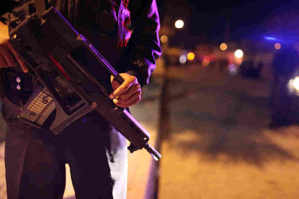 Police stand near the scene of a murder in Juarez, Mexico. The country suffers from drug cartel-related violence despite some of the most restrictive gun laws in the world.