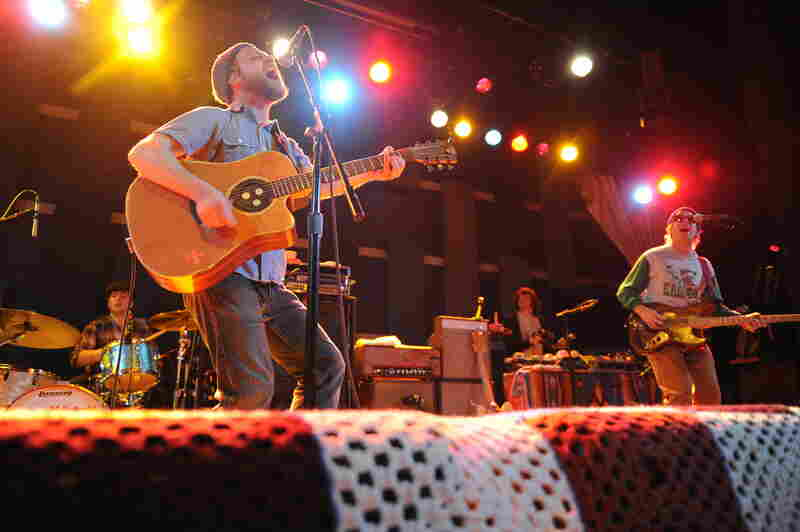 Toby Leaman (left, front) picks up an acoustic guitar while performing with Dr. Dog.