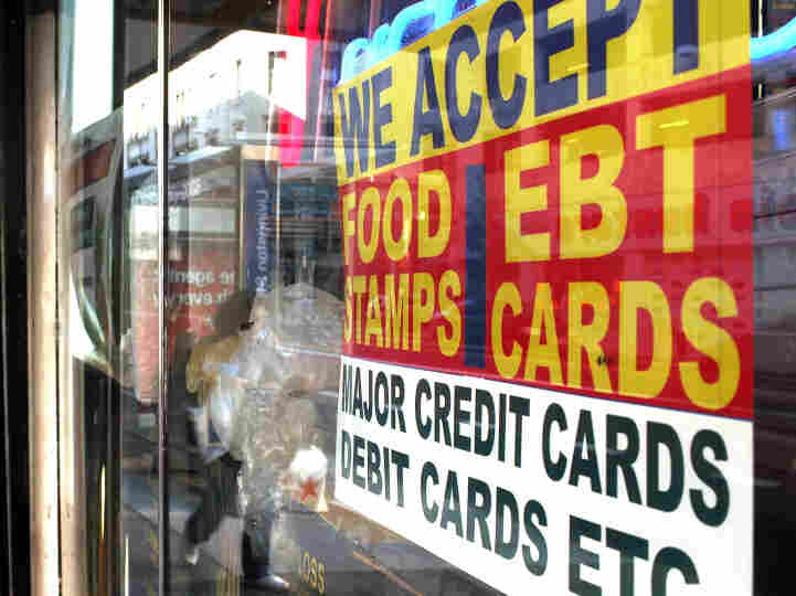 A sign in a New York City market window advertises that it accepts food stamps.