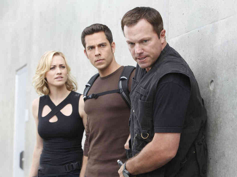 Yvonne Strahovski as Sarah Walker, Zachary Levi as Chuck Bartowski, and Adam Baldwin as John Casey in Chuck, which wraps tonight after five seasons.