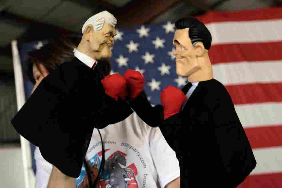 Lynn Coffin holds boxing hand puppets of former House Speaker Newt Gingrich (left) and former Massachusetts Gov. Mitt Romney during a campaign event this week in Sarasota, Fla.