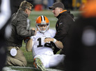 Trainers help Cleveland Browns quarterback Colt McCoy after he took a hit during a game in December. In a series of interviews with The Associated Press, 23 of 44 NFL players said they would try to hide a brain injury rather than leave a game.