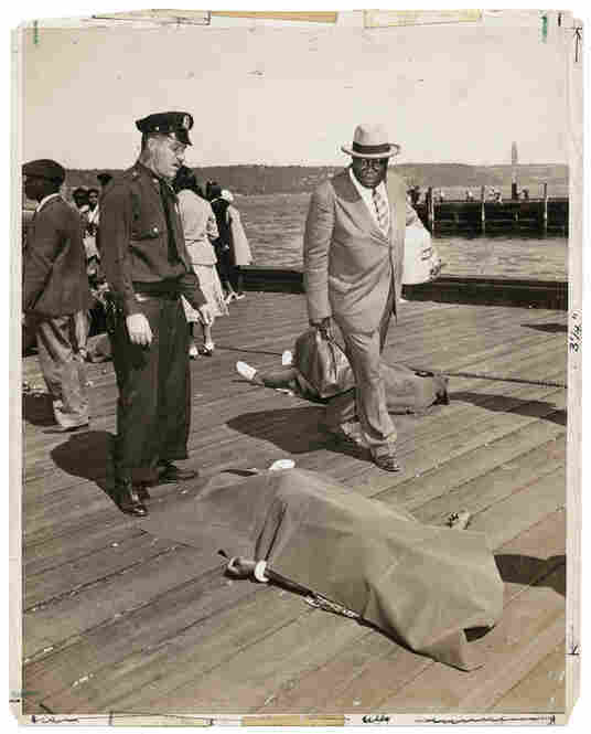 [Police officer and lodge member looking at blanket-covered body of woman trampled to death in excursion-ship stampede, New York], Aug. 18, 1941