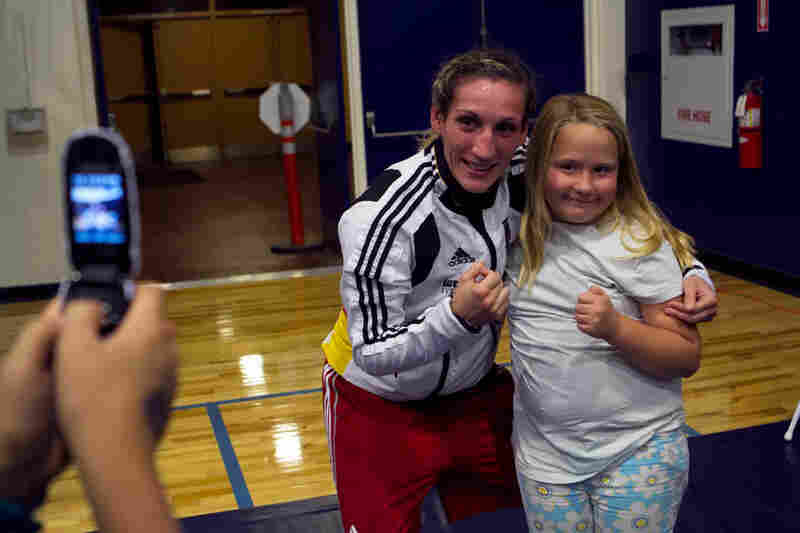 "Julia Irman won the German National Championship three weeks after giving birth to her son. Here, she poses with a young fan. ""In a couple years, I want to have another child. A girl. A boxer like me."""
