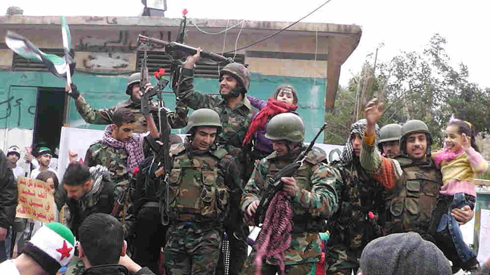 Syrian soldiers who defected join protesters in the al-Khaldiya neighborhood of the restive city of Homs on January 26, 2012.