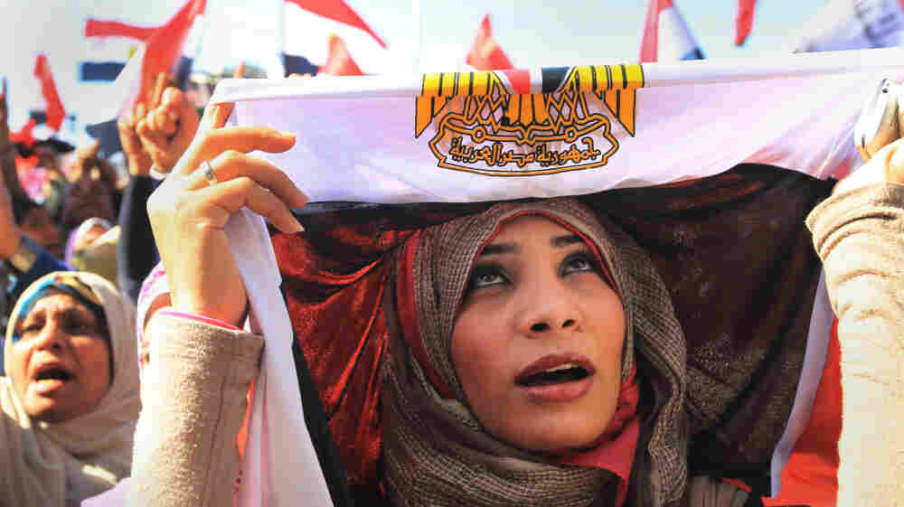 The U.S. is insisting that Egypt establish a full-fledged democracy and move away from military rule. Here, an Egyptian woman covers her head in a national flag as she demonstrates in a pro-democracy rally in Cairo's Tahrir Square on Jan. 27.