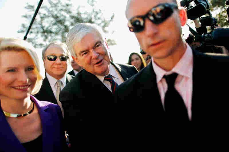 Newt and Callista Gingrich walk ahead of Michael Reagan (second from left), son of former President Ronald Reagan, outside a polling place in Windermere.