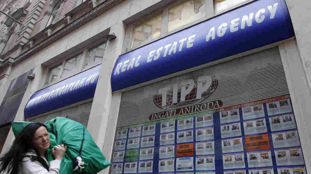 A woman passes by a real estate agency in Budapest, Hungary, in January. As the Hungarian currency plunges to new lows, ordinary citizens are struggling to repay foreign-denominated loans.