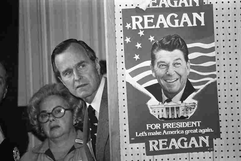 """George H.W. Bush lit into what he dubbed Ronald Reagan's """"voodoo economics"""" when the two competed for the 1980 GOP nomination. Bush peeks around a partition which has a poster of Reagan before he speaks in Columbia, S.C., March 4, 1980."""