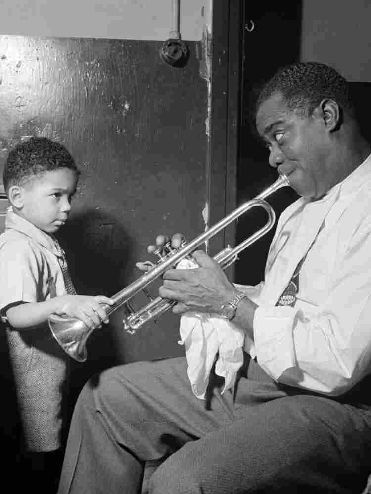 Louis Armstrong entertains a young fan backstage.