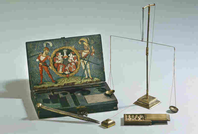 Beautifully decorated tools were constructed to balance and weigh gold and gemstones. This set has a wooden case covered with painted paper, iron and partially gilded silver.