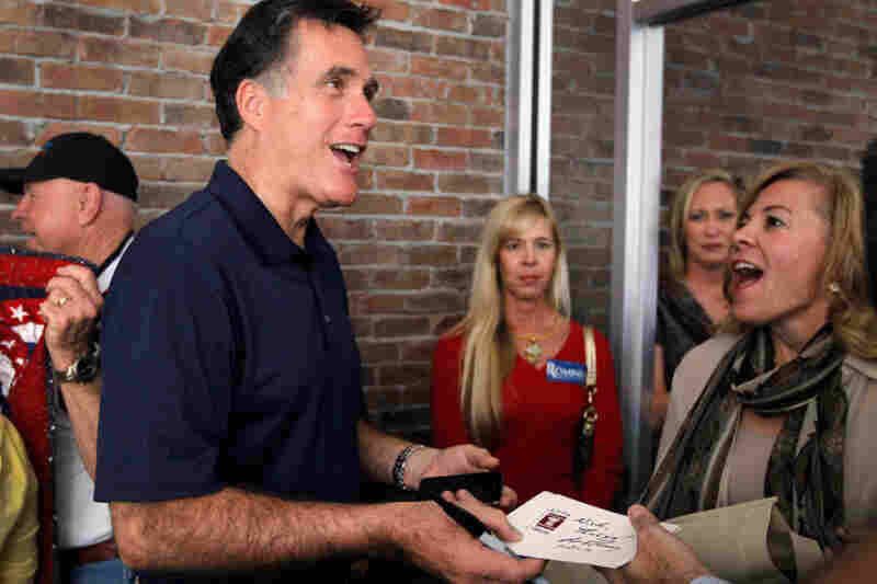 Romney greets supporters during a visit to his headquarters in Tampa.