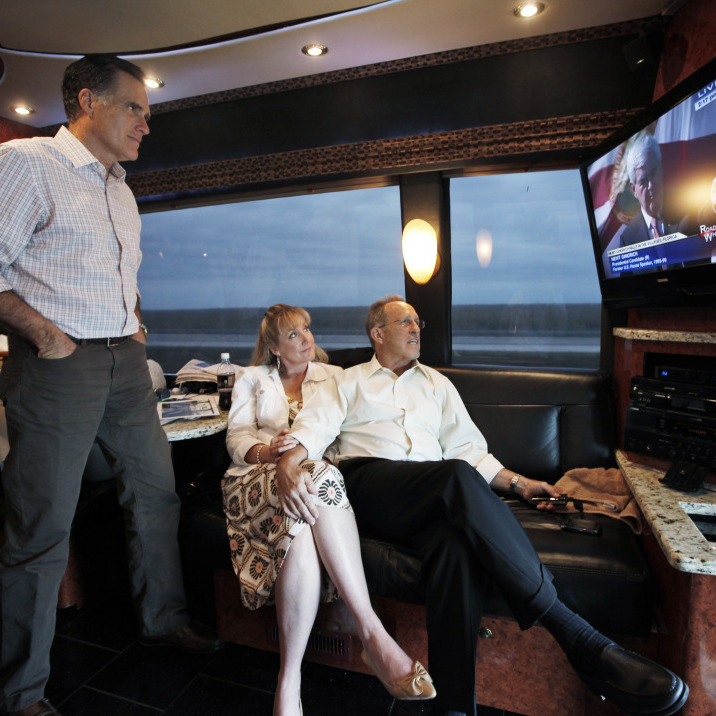 Mitt Romney watches his GOP rival Newt Gingrich on TV as he rides his campaign bus on Sunday with his brother Scott and sister-in-law Sheri. Using the power of television -- through ads and debates -- was a key part of Romney's strategy in Florida.