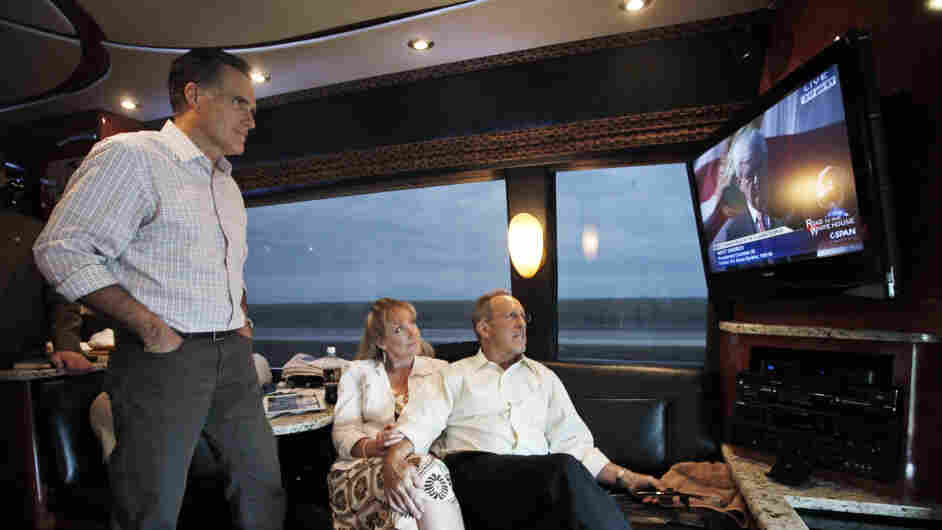 Mitt Romney watches his GOP rival Newt Gingrich on TV as he rides his campaign bus on Sunday with his brother Scott and sister-in-law Sheri. Using the power of television — through ads and debates — was a key part of Romney's strategy in Florida.