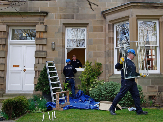 A glazier removes a smashed window at Goodwin's home  in Edinburgh, Scotland, after it was attack by vandals overnight on March 25, 2009. Public outrage ran high after the disgraced banker left his job with a pension of more than $1 million a year. Eventually, he agreed — reluctantly — to half that amount.